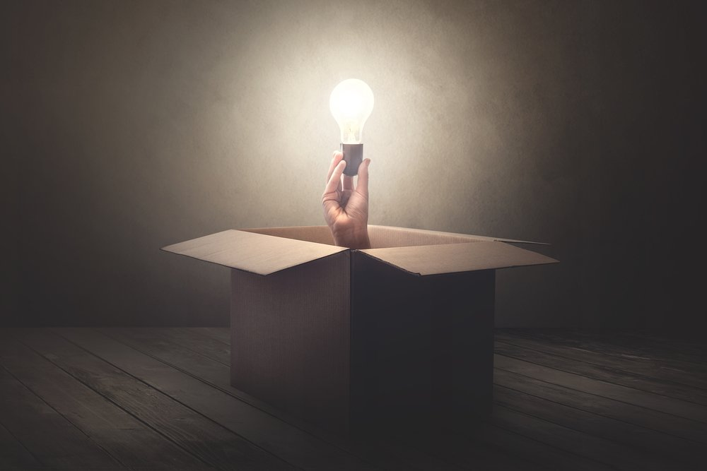 A cardboard box is centered in the image with a dark background. A hand holding a glowing light bulb emerges from the box.