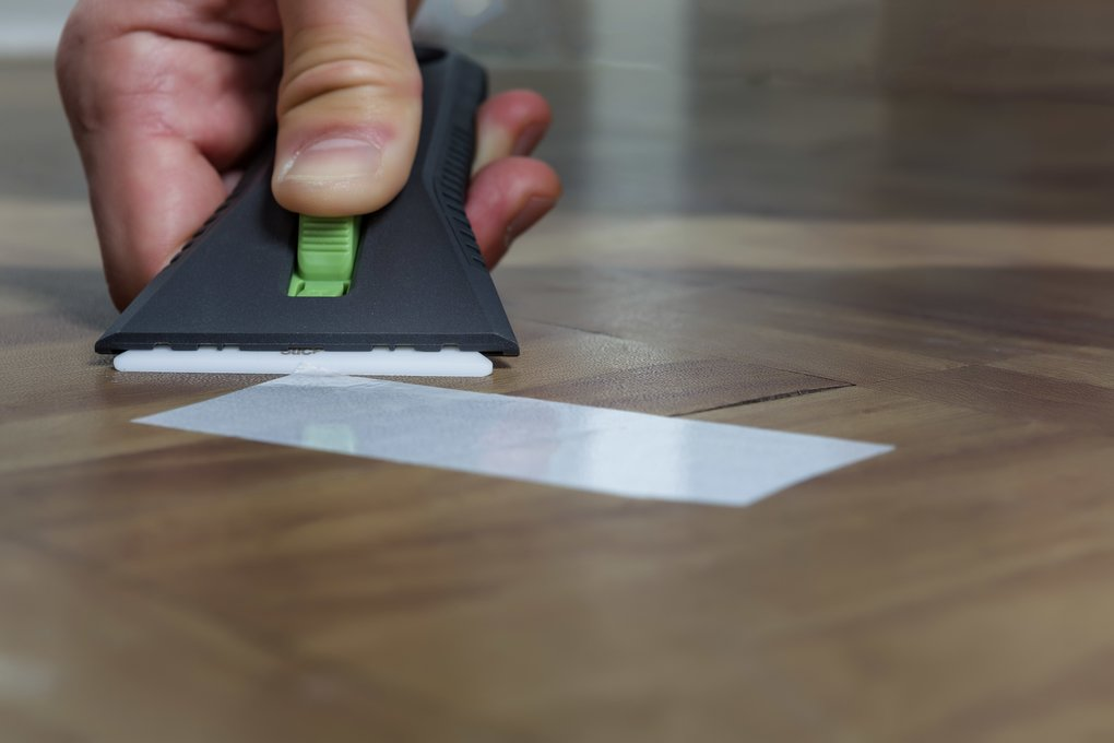 A Slice 10593 Auto-Retractable Ceramic Scraper being used to scrape adhered tape off a wooden surface.