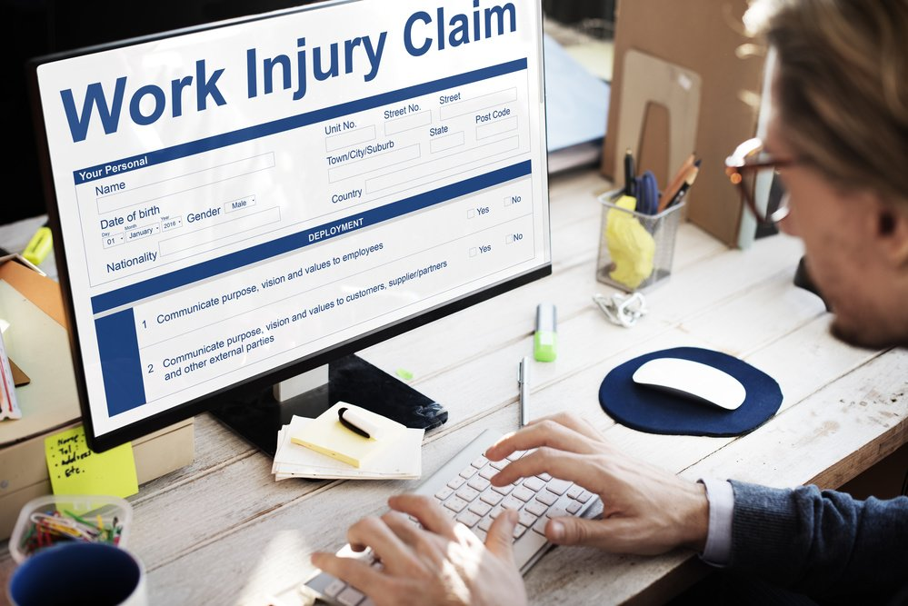 "Safety officer sitting at computer screen showing title of ""Work Injury Claim"" and showing costs of injury on screen"