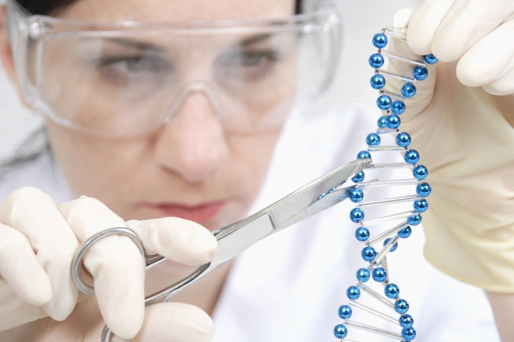 Female lab worker uses lab scissors to cut a blue double helix strand.