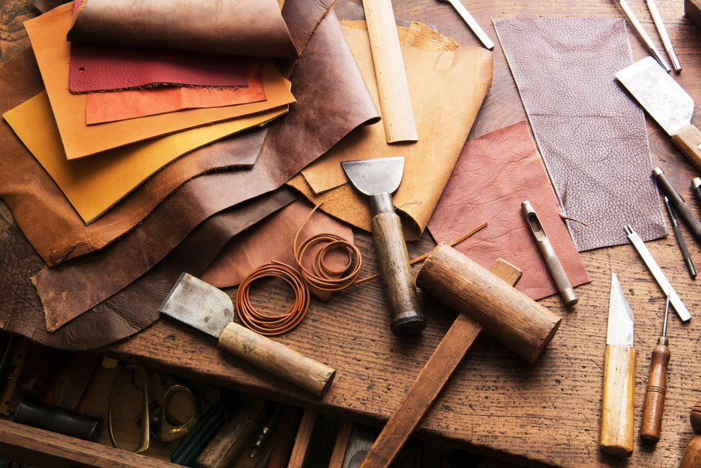 Leather pieces and leather cutting tools displayed on workbench